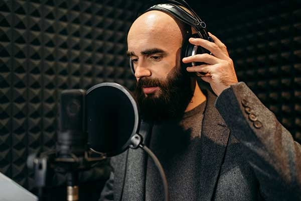 Bearded male voice actor speaks into a condenser microphone